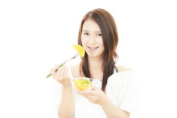 フルーツを食べる笑顔の女性