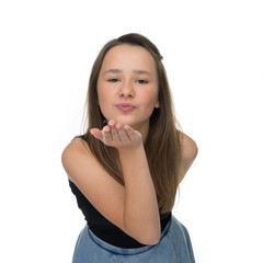Playful young girl blowing a romantic kiss