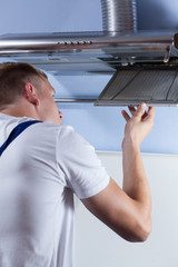 Man repairing kitchen hood