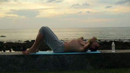 Man exercising with dumbbells by the sea in the evening