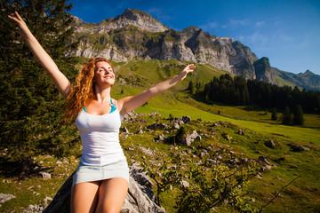 glückliche junge Frau in Alpen-Landschaft
