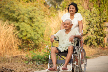 Senior woman pushing her disabled husband on wheelchair