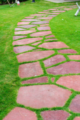 Stone walk path in the park with green grass