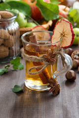 apple cider with spices in a glass cup, vertical