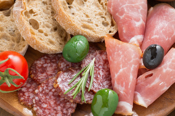 assorted Italian antipasti - deli meats, olives, bread