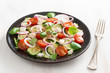 vegetable salad with feta cheese on white wooden table