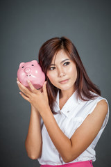Beautiful Asian girl wonder how much money in piggy bank