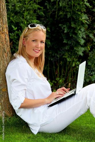 canvas print picture Frau mit Laptop Computer im Garten
