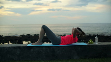Young woman doing sit-ups, exercising by the sea in the evening
