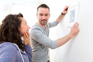 Couple hanging a painting in their new flat