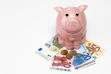 Rosa Sparschwein mit Geld auf weißem Hintergrund