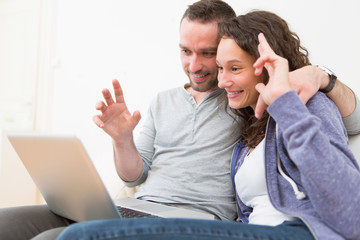 Young happy couple video calling on computer