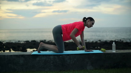 Young woman exercising with dumbbells by the sea in the evening