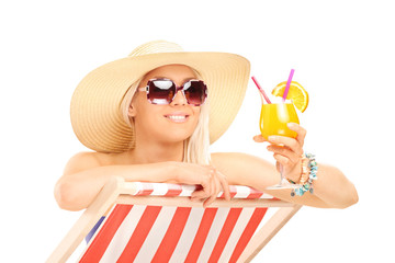 Trendy woman drinking a cocktail on a sun lounger