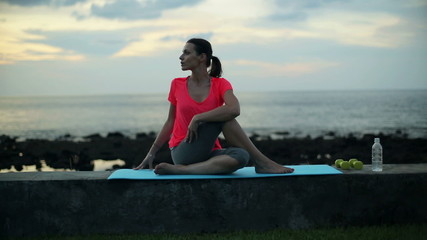 Young woman stretching, exercising by the sea in the evening