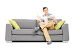 Peaceful young man reading the news seated on sofa