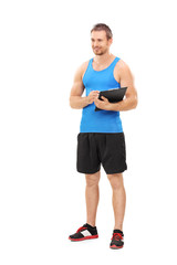 Full length portrait of a fitness coach holding a clipboard