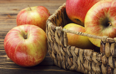 Red apples and basket on wooden background