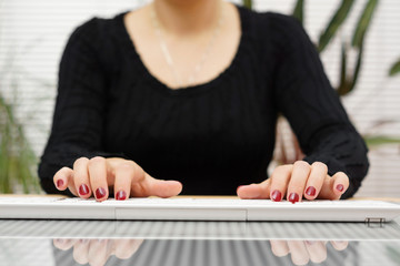 front view  woman is typing on white  keyboard at home