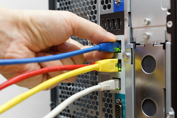 system administrator connecting network cables to data server