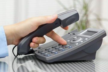 businessman hand is dialing a phone number with picked up headse