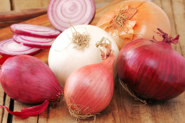 Different types of onion on wooden table