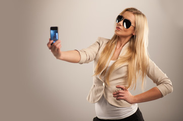 Happy young girl taking pictures of herself.