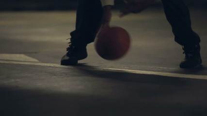 Basketball player dribbling the ball quickly at night