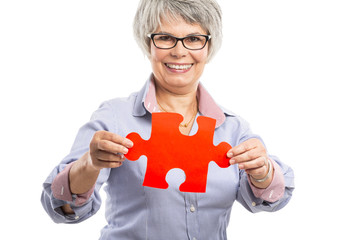 Elderly woman holding a puzzle piece