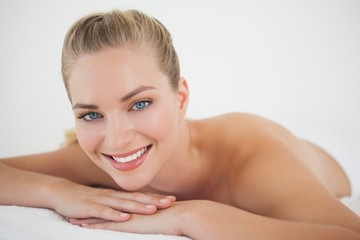 Beautiful blonde relaxing on massage table smiling at camera