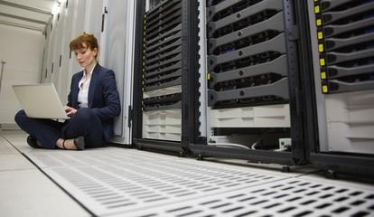Technician sitting on floor beside server tower using laptop