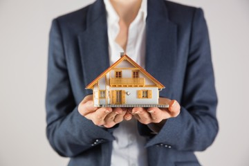 Businesswoman holding miniature model house