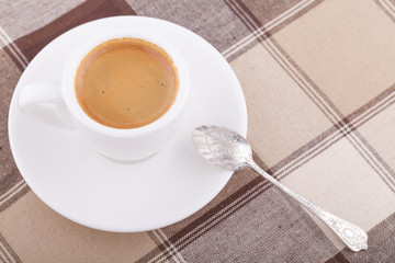 White cup of coffee on tablecloth