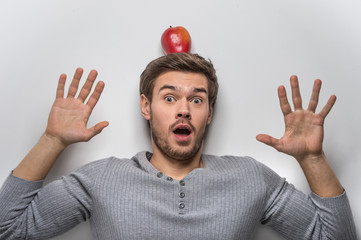 Handsome young guy balancing red apple on his head