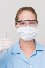 Dental assistant in mask holding dental explorer