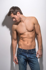 Healthy muscular young man in jeans.