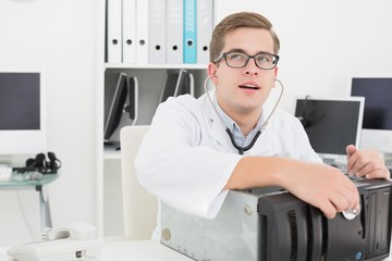 Computer engineer listening to console with stethoscope