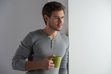 Thoughtful man having coffee and leaning on wall.