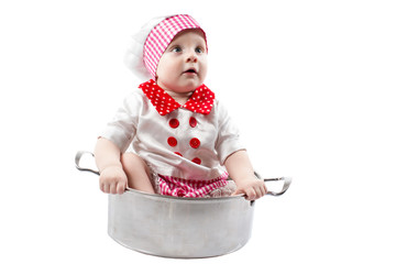Baby cook boy wearing chef hat with fresh vegetables