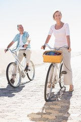 Happy senior couple going for a bike ride