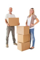 Happy couple smiling at camera with moving boxes