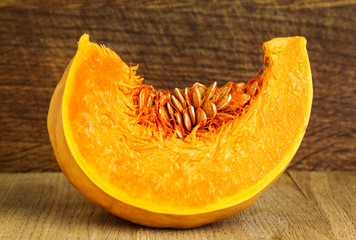 Slice of pumpkin on wood background