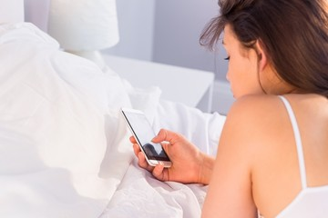 Beautiful brunette lying on bed using her smartphone