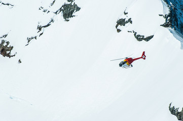 Red Helichopter flying above snow mountain in Jungfrau Region