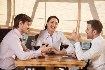 Three young friends having wine together in cafe.
