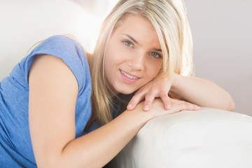 Smiling young woman lying on sofa in living room