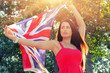 Young brunette holding UK flag in her outstretched hands