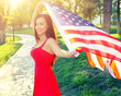 Happy young woman holding american flag. Cute female in red dres