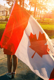 Women with Canada nation flag in her hands outdoors from back vi - Fine Art prints