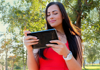 Beautiful Young Woman With Tablet Computer In Park. Female stude